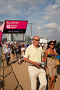 London, UK. Thursday 9th August 2012. London 2012 Olympic Games Park in Stratford. People arriving at the park underneath an entrance sign in the late afternoon light.