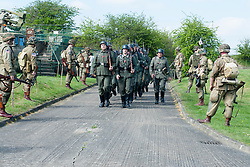 Axis Reenactors of the NWW2A drill at Fort Paull on Sunday watched by other reenactors portraying members of the US 82nd Airborne..5 May 2013.Image © Paul David Drabble