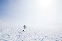 A woman making her way up a steep snow field wearing a heavy backpack. Seattle Park, Mount Rainier National Park, Washington, USA.