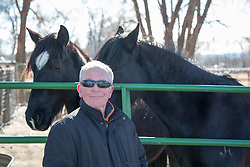middle aged man near horses