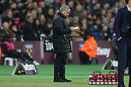 Jose Mourinho, the Manchester United manager looks at his notes on the touchline. Premier league match, West Ham Utd v Manchester Utd at the London Stadium, Queen Elizabeth Olympic Park in London on Monday 2nd January 2017.<br /> pic by John Patrick Fletcher, Andrew Orchard sports photography.