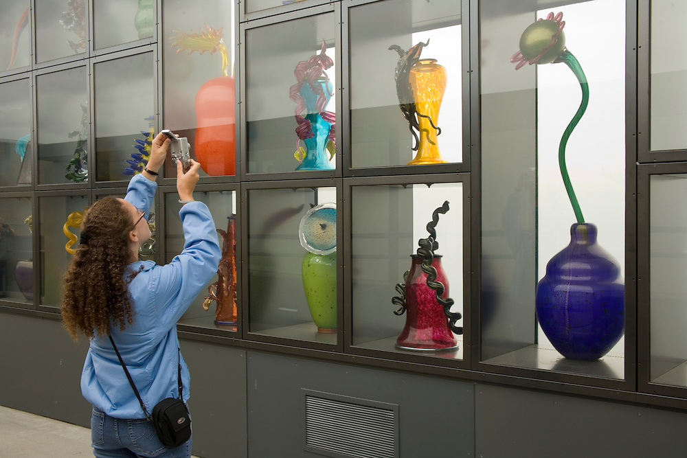 Teenage girl (age 16) takes digital photograph of Venetian Wall, glass art by Dale Chihully on Chilhuly Bridge of Glass near Museum of Glass, Tacoma, Washington, USA  MR