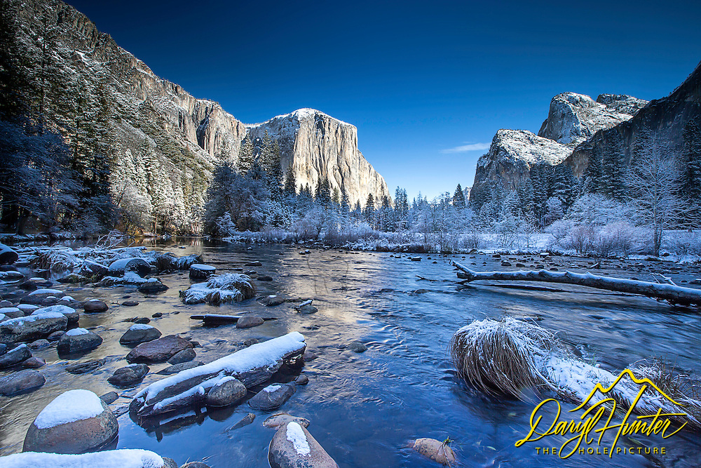 Winter in Yosemite Valley.  Blankets of snow highlight the rocks, grassy tufts, and logs of the Merced River as it winds its way from the high Sierra to a thirsty California below.