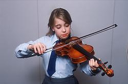 Young girl wearing school uniform playing violin,