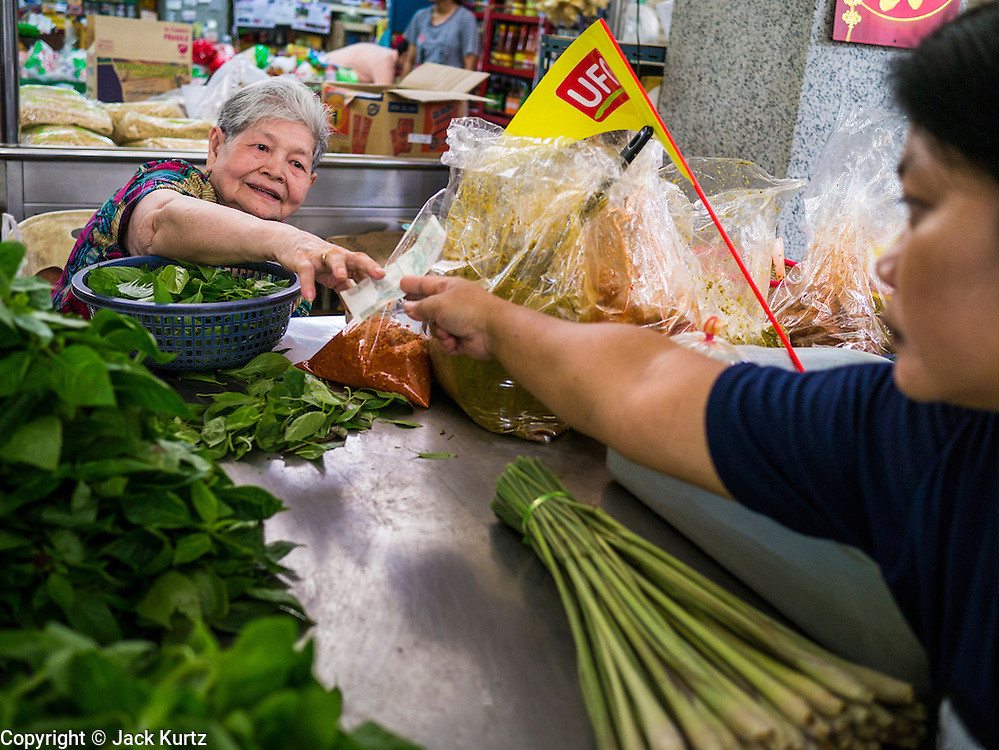 12 OCTOBER 2012 - NAKHON PATHOM, NAKHON PATHOM, THAILAND: A vendor accepts cash for a purchase from a customer in the Nakhon Pathom market.   PHOTO BY JACK KURTZ