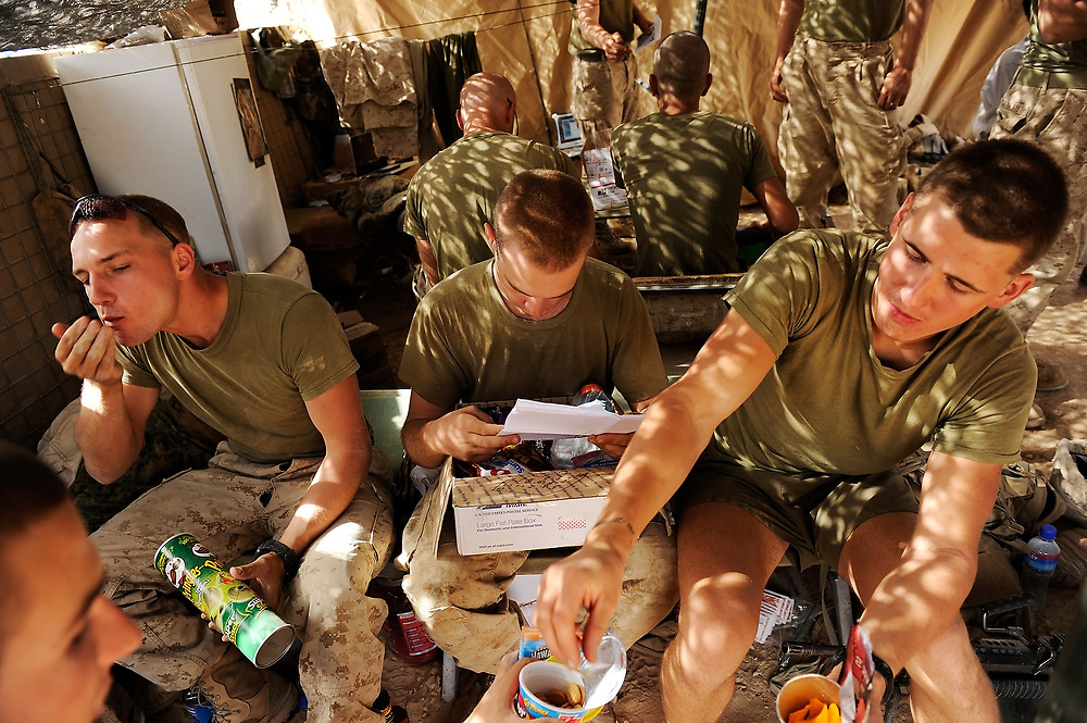 9/7/10 1:08:56 AM -- -- <br /> 1st Battalion, 2nd Marine Regiment, Charlie Company, 1st platoon LCPL's Brandon Raddatz, left, Matthew Dickens, center, and Dimitry Bludov, right, share in a care package sent by the brother of Dickens as the squad received a welcomed shipment of mail and packages from home to the marines remote outpost Kunjak near Musa Qala, Helmand Province, Afghanistan in the daytime heat of Helmand Province.<br /> <br /> Photo by Jack Gruber, USA TODAY Staff