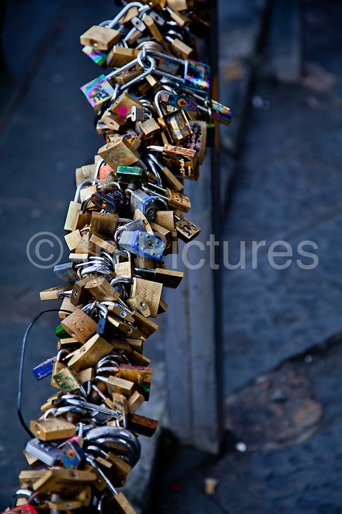 """Cycle locks outside the Uffizi gallery, Florence. Florence has decided to stamp out a tradition which has recently drawn thousands of young lovers to the city's famous Ponte Vecchio bridge. Enamoured couples have been going to the bridge to attach padlocks to a bronze bust and the railings around it. The act is seen as symbolising the 'unbreakable' bonds uniting them.<br /> <br /> The result, according to grumpy council officials, has been a proliferation of unsightly clusters of metal disfiguring the monument to Benvenuto Cellini, one of the city's most famous artistic sons. In the winter of 2011 the council set a team of metal cutters to work removing the 5,500 locks which had accumulated on the railings. Meanwhile, city police have been told to watch over the busy tourist site and to slap a 50-euro fine on anyone who tries to attach a lock. The work of removing the """"lucchetti d'amore"""" took a long time because workmen were battling against a never-ending flow of loving couples who arrived in Florence and made straight for the Ponte Vecchio"""