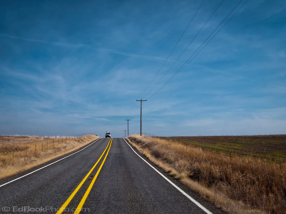 A loaded vehicle comes into view over a crest in the road with a contrail overhead in rural Klickitat County, WA, USA