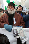 Moscow, Russia, 04/02/2012..A man with a partly frozen beard hold photographs of Russian President Vladimir Putin and jailed oligarch Mikhail Khordokovsky, as tens of thousands of demonstrators march in central Moscow and protest against election fraud and Prime Minister Vladimir Putin in temperatures of -20 centigrade. Organisers claimed an attendance of 130,000 despite the bitter cold.