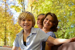 Family sitting on bench, smiling, portrait, Bavaria, Germany