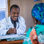 INDIVIDUAL(S) PHOTOGRAPHED: Getachew Anteneh (left). LOCATION: Mecha Health Center, Bahir Dar, Ethiopia. CAPTION: Health Officer Getachew Anteneh smiles as he gives a patient advice on HIV/AIDS.