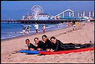 Four (4) young women learn to surf in Santa Monica, California near the Santa Monica Pier.