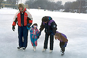 Family ice skating on frozen pond during winter ages 35 4 and 6. Brackett Park Minneapolis  Minnesota USA