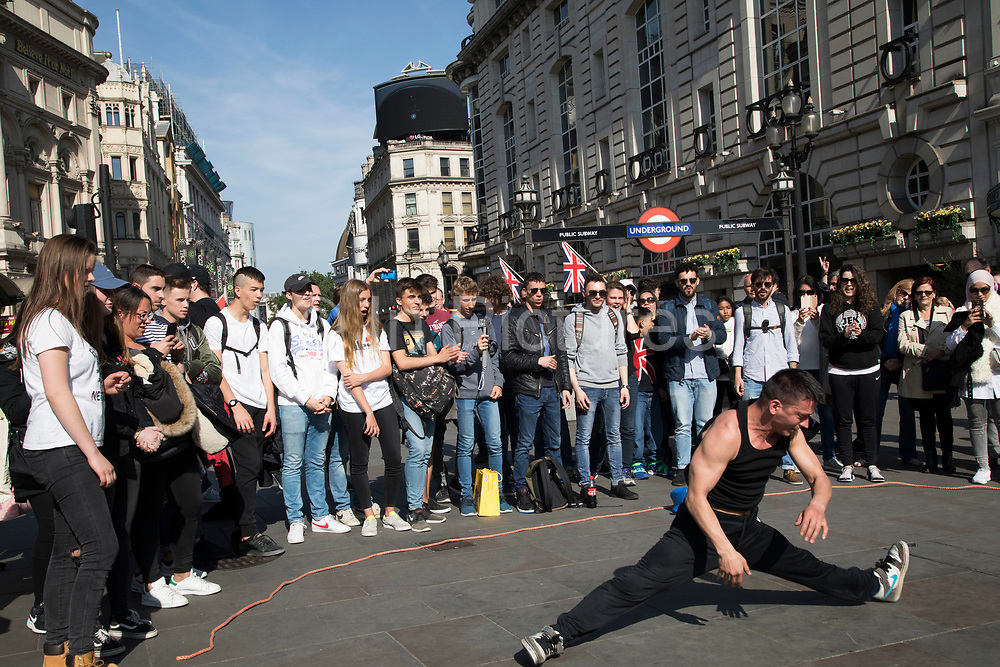 Tourists gather to watch street performers breakdancing show at Piccadilly Circus in London, England, United Kingdom.