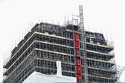 © Licensed to London News Pictures. 21/05/2018. LONDON, UK.  A workman in a safety helmet at work behind scaffolding which currently covers the burned out shell of the Grenfell Tower in West London on the day that commemoration hearings begin in the Millennium Gloucester hotel.  Over the next nine days, friends and family will be paying tributes to the 72 victims killed by the fire in the building nearly one year ago.  Photo credit: Stephen Chung/LNP