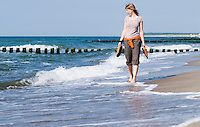 Single female walking barefoot in gentle waves of Baltic coast, Germany