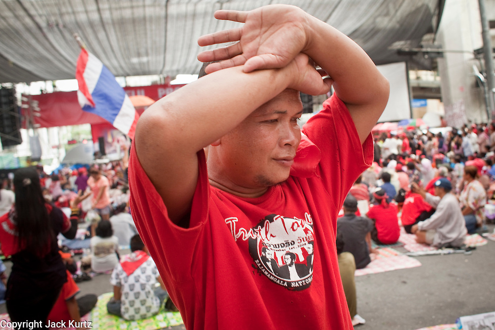 """May 12 - BANGKOK, THAILAND: A Red Shirt protester walks away from the main stage as word of an anticipated government crackdown spread. The Thai government said Wednesday that time has run out for """"Red Shirt"""" protesters in Ratchaprasong and Sala Daeng intersections in Bangkok and that a crackdown could come at any time. As news of the anticipated crackdown spread, Red Shirt protesters continued with an almost festive mood at their main stage but many of the sleeping areas around the protest site appeared to be empty. No official estimates on crowd size are available.  Photo by Jack Kurtz"""