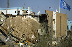 People rush to free UN workers trapped in the rubble at the Canal Hotel where a cement truck packed with explosives detonated outside the offices killing 20 people and devastating the facility in Baghdad, Iraq on Aug. 19, 2003. This was an unprecedented suicide attack against the world body with at least 100 people wounded.