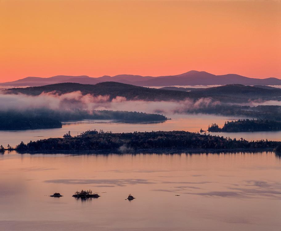 Rising fog & brilliant dawn color, Squam Lake & Belknap mountains, Holderness, NH