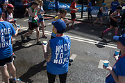Lucozade support tema hand out drinks to participants taking part in the London Marathon on 22nd April 2018 in London, England, United Kingdom. The London Marathon, presently known through sponsorship as the Virgin Money London Marathon, is a long-distance running event. The event was first run in 1981 and has been held in the spring of every year since. The race is mainly known for ebing a public race where ordinary people can challenge themsleves while raising great amounts of money for various charities.