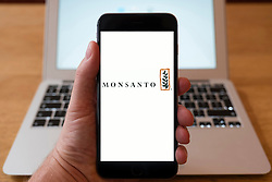 Using iPhone smartphone to display logo of Monsanto ;multinational agrochemical and agricultural biotechnology corporation