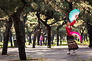 An elderly Chinese woman practices tai chi fan dance martial arts exercise early morning at the Temple of Heaven Park during summer in Beijing, China