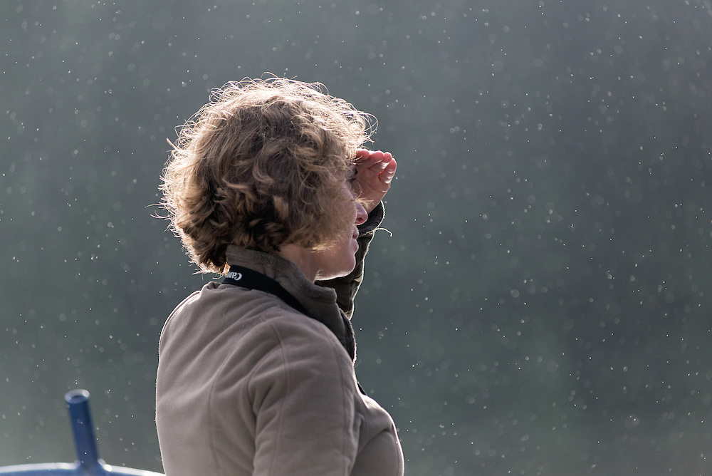 Portrait of a woman looking out from the deck of a boat in light rain, Southeast Alaska.