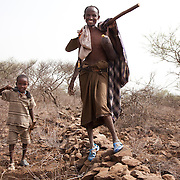 Ali and his 5 year old son Umah. Umah is with his dad at work because his mother is herself busy at work somewhere else. Ali only work in the morning and they both head home before it gets too hot. The stone wall project is to prevent precious top soil to be washed away when the rain does come and AISDA employ locals to build walls running across the hill side.  Action for Integrated Sustainable Development Association (AISDA) work in the AFAR region of Eastern Ethiopia, based in Delafagi. The Afars practise an old tradition of Female Genital Mutilation where the baby girls has her clitoris and labia cut away and her vagina sewn up. The day before her wedding day the girl is un-stiched ready for marriage. Its a brutal and barbaric tradition which AISDA is challenging with great effect, now more than a hundred girls in Dowe district have been saved from the knife and AISDA is now rolling out the scheme in Delafagi. Delafagi is where the oldest ever human remains have been found, the found is thought to be 4.5 mill years old.