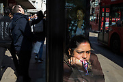 Woman at a bus stop on Oxford Street waits patiently as life goes on around her in London, United Kingdom. She was in her own little world with her chin on her hand staring out of the window with the hustle and bustle of Londons well known shopping street going on around her.