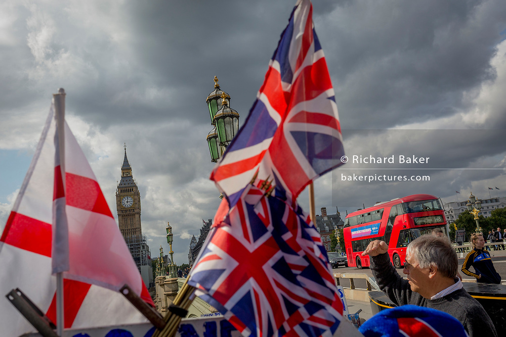 Union Jack flags and a red London Routemaster bus on Westminster Bridge and the Houses of Parliament over in Westminster, on 12th September 2017, in London, England.