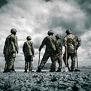A group of British soldiers resting whilst on manoeuvres, shot against a stormy sky.