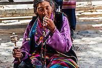 A Tibetan pilgrim spinning a prayer wheel outside the  Tashilimphu Monastery, Shigatse, Tibet (Xizang), China.