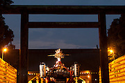 People carry a mikoshi or portable shrine past a wall of yellow lanterns, each containing the name of a fallen serviceman, towards a large torii gate during the Mitama matsuri in remembrance of Japan`s war dead at the controversial Yasukuni Shrine in Tokyo, Japan. Sunday, July 13th 2008