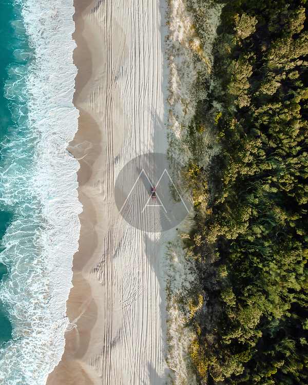 Aerial view of a car driving on the beach, Bribie Island, Queensland, Australia. Top down perspective.