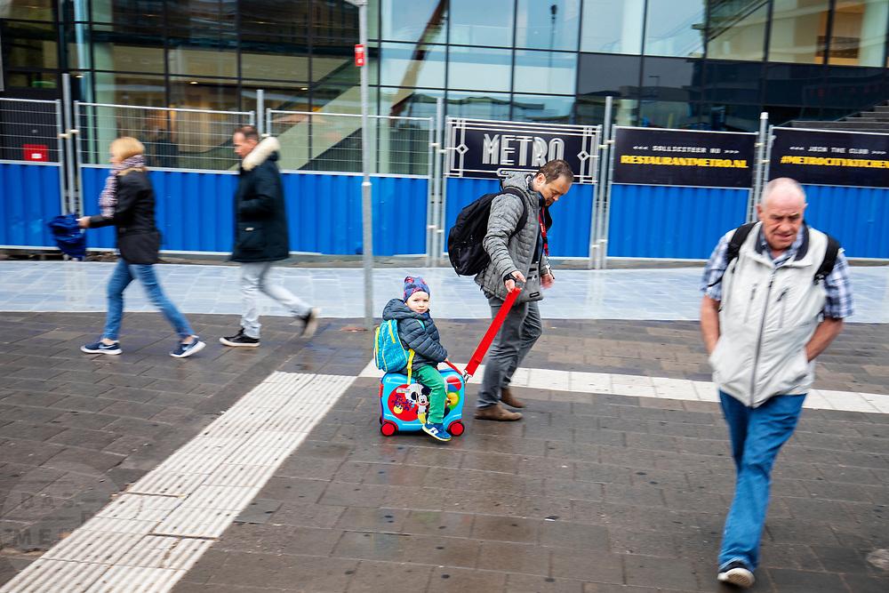Een jongetje wordt bij station Utrecht zittend op een koffer voortgetrokken door zijn vader.<br /> <br /> A boy sitting on a suitcase is being pulled by his father at Utrecht Central Station