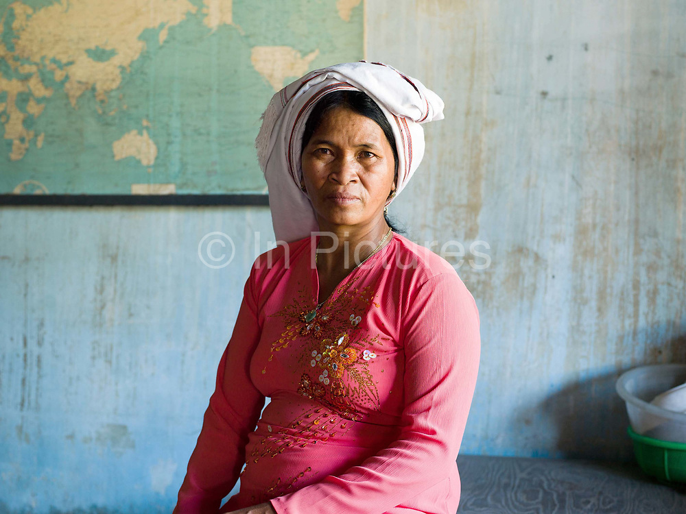 Portrait of a Cham woman wearing a traditional Cham white headscarf and an Ao Dai, the national Vietnamese dress in Song Pha village, Lam Dong province, Central Vietnam