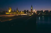 It is dusk and the evening light is fast-disappearing behind the buildings of Westminster, London. Seen from the south bank of the River Thames and looking over Westminster Bridge, traffic lights trail and the light fades over the Palace of Westminster and the tall clock tower of Big Ben, London England. Street lights flare intensively during the long-exposure and there is enough ambient light to see the reflections on the river's water. The Palace, also known as the Houses of Parliament or Westminster Palace, is where the two Houses of the Parliament of the United Kingdom (the House of Lords and the House of Commons) conduct their business. It is therefore a potent symbol for British Governmental power, influence and a world-famous landmark for tourists. Big Ben is the name of the clock's bell and not the tower itself.