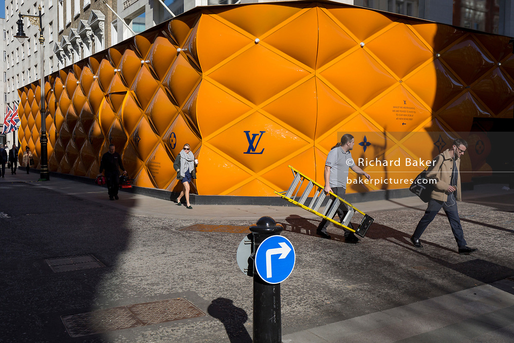 A workman carries stepladders across the road opposite the temporary renovation hoarding of luxury brand Louis Vuitton in New Bond Street, on 25th February 2019, in London, England.