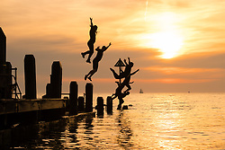 ©Licenced to London News Pictures<br /> 25 June 2018 . Aberystwyth Wales UK<br /> UK Weather:  A group of young people  in silhouette jumping into the sea together off the jetty on Aberystwyth beach at dusk at the end of another glorious day of hot unbroken sunshine.<br /> The UK is heading  into a mini heatwave, with temperatures forecast to hit 29º or 30º Celsius by the middle of the week<br /> <br /> photo credid Keith Morris / LNP