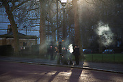 Smoking and vaping in the sunlight near St Jamess park in London, England, United Kingdom. Both smokers and vapers have to go outside to smoke or vape due to laws protecting our air in public and work places.
