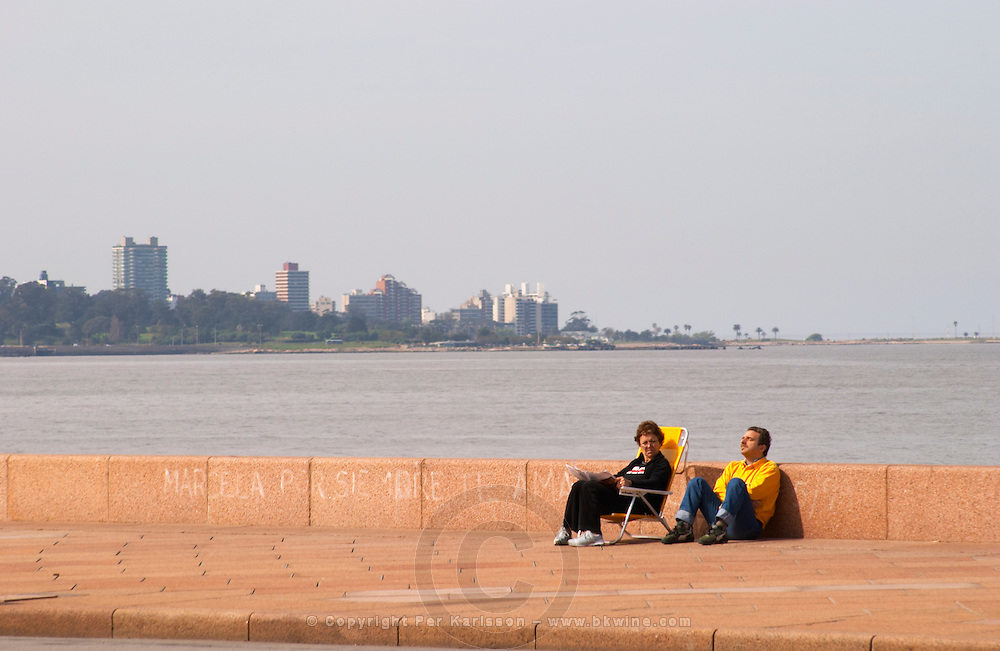 The coastal walk with the city skyline and two people sitting relaxing on folding chairs along the water. along the river riverside coast walk Rio de la Plata Ramblas Sur, Gran Bretagna and Republica Argentina Montevideo, Uruguay, South America