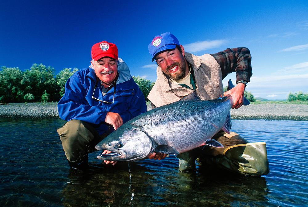 Alaska. Crystal Creek lodge and guests with prize catch of a King Salmon (Chinook)