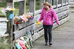 © Licensed to London News Pictures. 23/08/2015. Shoreham, UK.  People laying flowers and pay their respect at the footbridge heading to the crash site. Emergency services and Dozens of support vehicles are still visible at the scene where a Hawker Hunter fighter jet crashed in to cars on the A27 road in front of thousands of spectators at the Shoreham Airshow in West Sussex with 7 people confirmed dead. Today August 23rd 2015. Photo credit : Hugo Michiels/LNP
