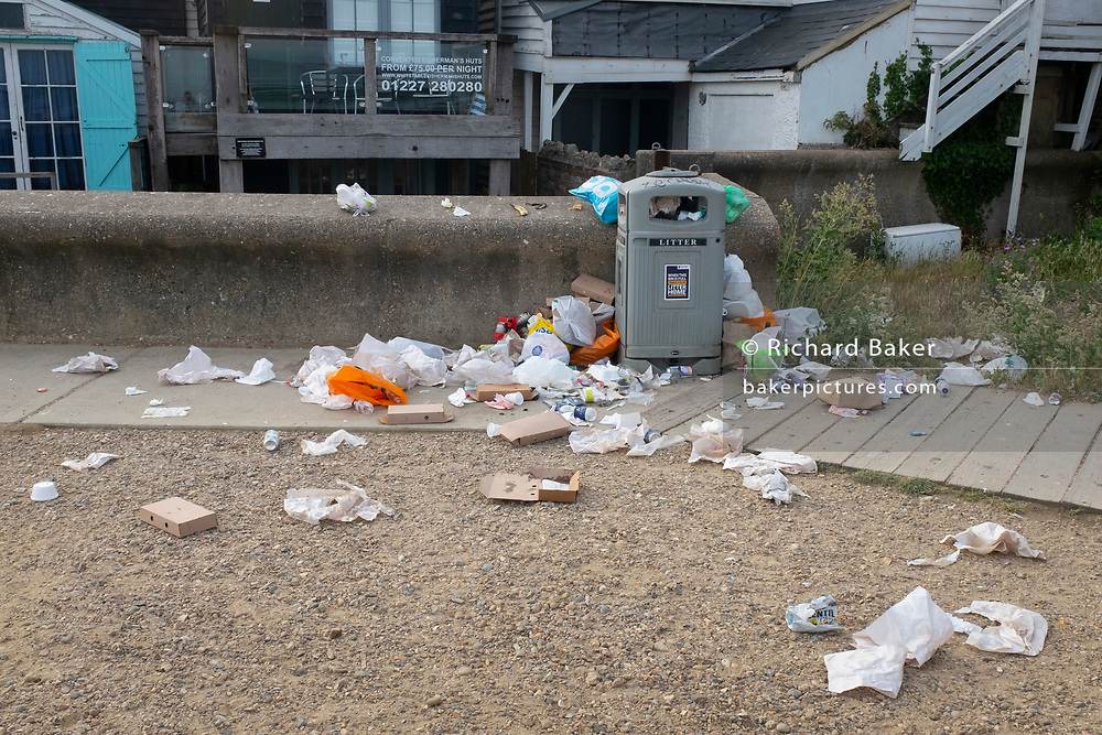 The morning after Saturday night crowds of young peoples' nightlife beach parties, their litter and rubbish from the night before stretches across the coastal paths and shingle, locals wanting a quiet morning walk are confronted by a mess along the sea wall, on 19th July 2020, in Whitstable, Kent, England.  A group of local volunteers and council cleaner will soon arrive for the regular morning clean-up that has got worse, they say, during the Coronavirus pandemic lockdown and now, the slow easing of health guidelines.
