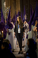 A woman checks the flow of procession inside the Mezquita. Every Holy Week procession in Cordoba, coming from all neighbourhood, walks past and inside the UNESCO heritage Cathedral. A meticulous timing and organisation assure everything goes smoothly. Andalusia, Spain
