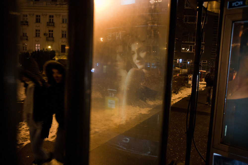 Reflection of an advertisement for perfume at a bus stop in the city center.