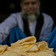 A muslim shop keeper selling Halwa Puri, deep fried bread stuffed with sweet halwa. Kolkata, January 2007