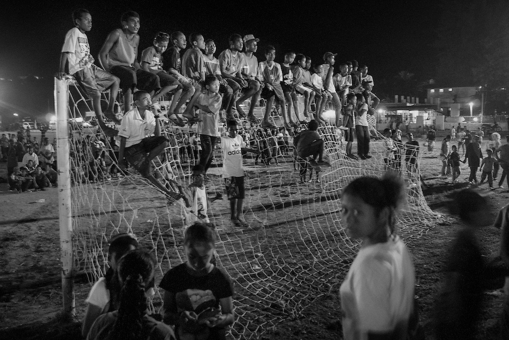 """Crowd gathers at a night market in Sorong, West Papua. Non-Papuans now outnumber ethnic Papuans. <br /> <br /> Papua is a vast province and has abundant natural resources such as copper, gold, and timber.  However, most indigenous Papuans live on less than $1 a day.  The incidence of poverty in Papua is the highest in the country; double that of the national average.  Papua was acquired by Indonesia in 1969 in a disputed vote rejected by most Papuans.  For the past four decades Papuans have sought independence.  A transmigration policy implemented by the federal government relocated almost a million non-Papuan migrants from surrounding provinces as part of the """"Indonesianization"""" process.  These migrants, along with another million voluntary migrants, dominate most of the region's trade and business, thereby controlling authority and dictating commerce in Papua.  Imported goods such as rice, medication, and gas are brought into Papua and sold at exorbitant prices, making the cost of living the highest in Indonesia.  Coupled with unequal access to education and training, opportunities for indigenous Papuans to advance economically are limited.  The consequence is economic inequality¬--wealthy migrants and poor Papuans--and a marginalized indigenous population where poverty, unemployment, malnourishment, illness, illiteracy, and discrimination are the norm."""
