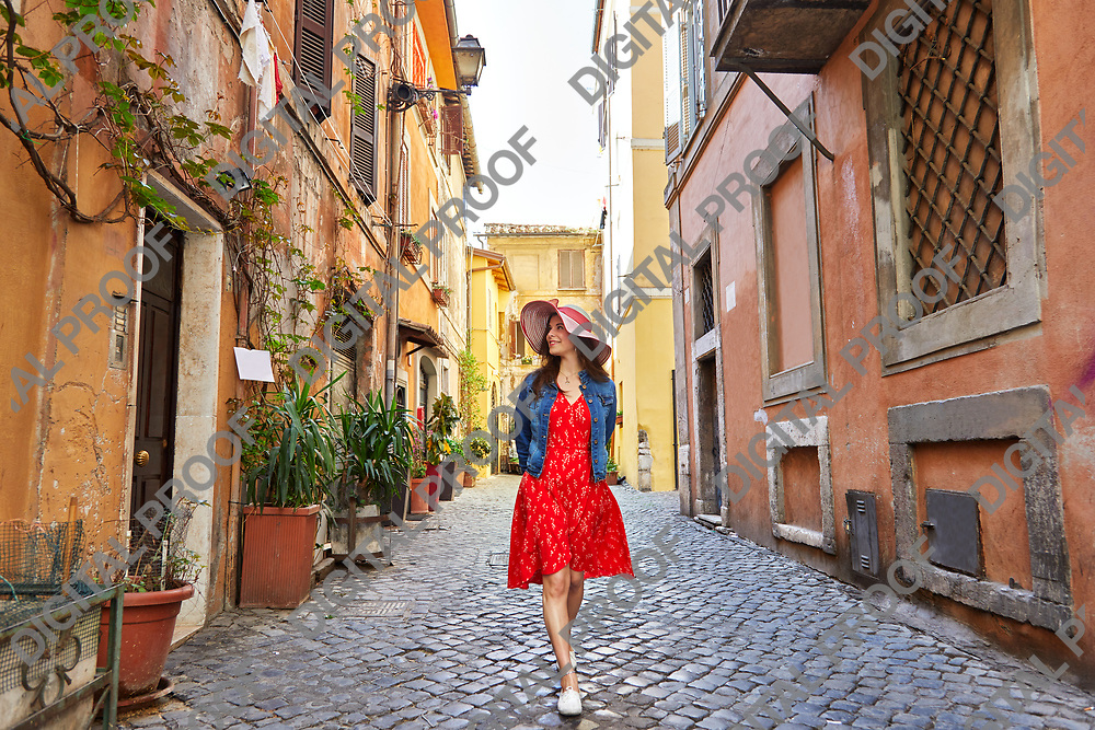 Pretty young tourist woman in hat walking at Trastevere in Rome, Italy.