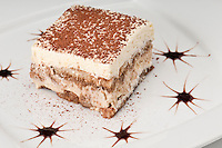 Plate of tiramisu cake decorated in a restaurant.